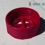 Close up image of a deep magenta intake valve. It has 40mm NATO threading.
